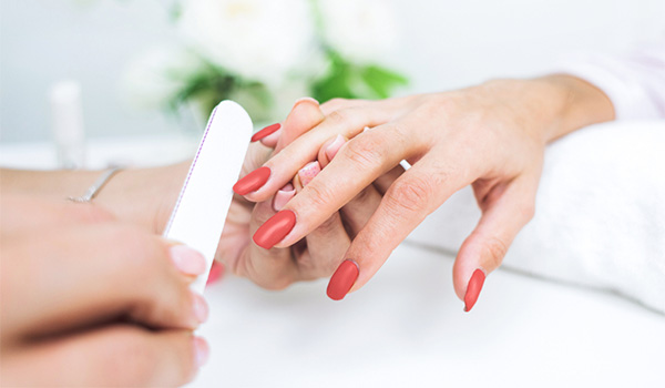 Woman having her nails painted pink