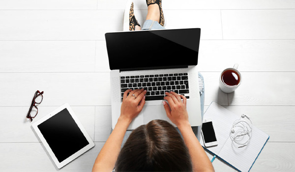 Overhead view of a woman typing on a laptop