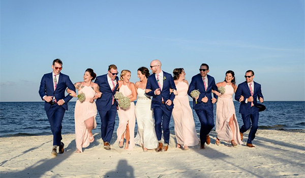 Bride, groom, bridesmaids and groomsmen walking along the beach