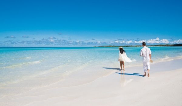 Couple walking down a pristine white-sand beach