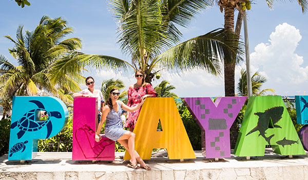 Tessa and her two friends posing by the colourful Playa Del Carmen sign