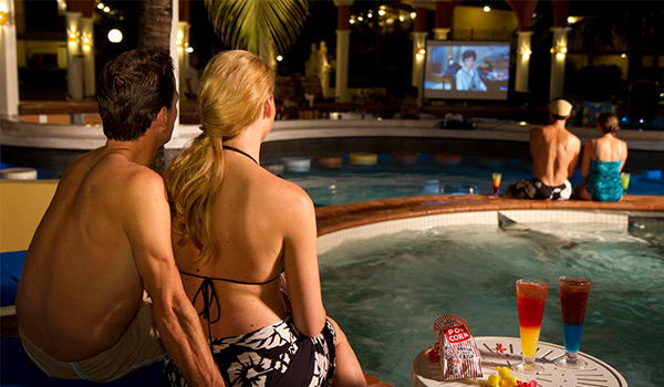 Couple sitting by the pool watching a movie on a projector screen