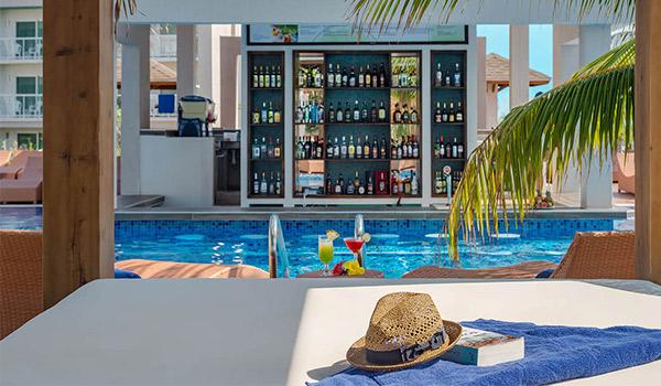 Chapeau et livre sur un lit balinais ombragé avec vue sur un bar dans la piscine