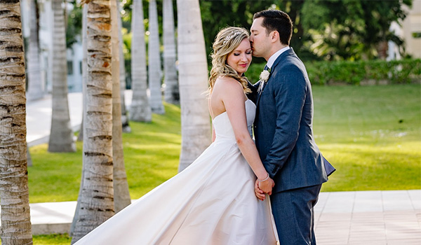 Groom and bride posing in a garden surrounded by palm trees