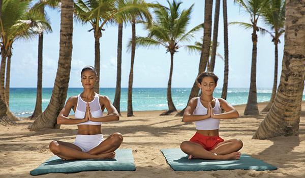 Une mère et sa fille faisant du yoga sur la plage.