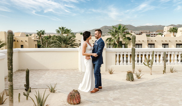 Wedding couple standing on a terrace surrounded by cacti