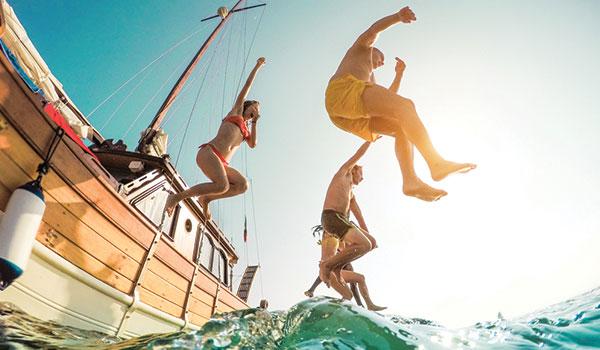 Vue du dessous d'un groupe de personnes sautant d'un bateau dans l'eau