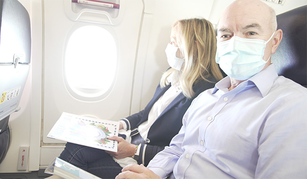 Dr. Nord and his wife wearing masks on the plane
