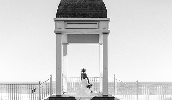 Bride sitting on the steps of a stone gazebo