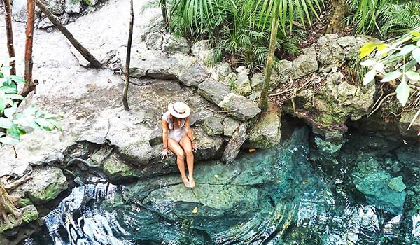 Woman sitting on the edge of a cenote in the jungle