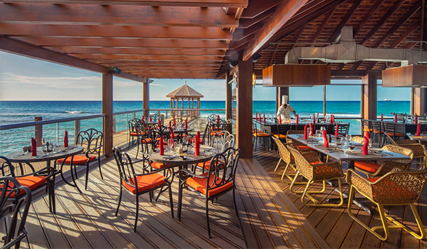 Open air restaurant on a pier with Teppanyaki tables overlooking an oceanside gazebo