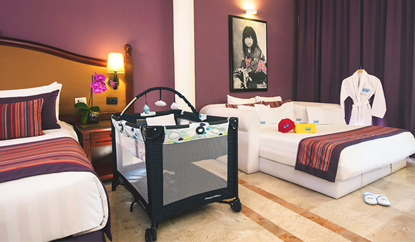 Two beds and a crib in a spacious suite
