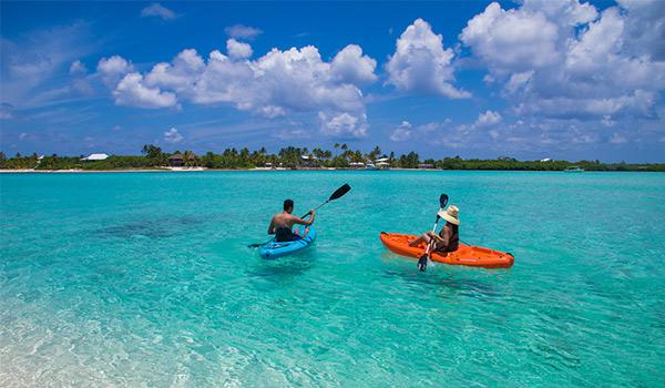 Deux personnes sur des planches à bras dans les eaux bleues étincelantes du Grand Caïman