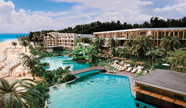Aerial view of resort pools overlooking the beach surrounded by jungle landscapes