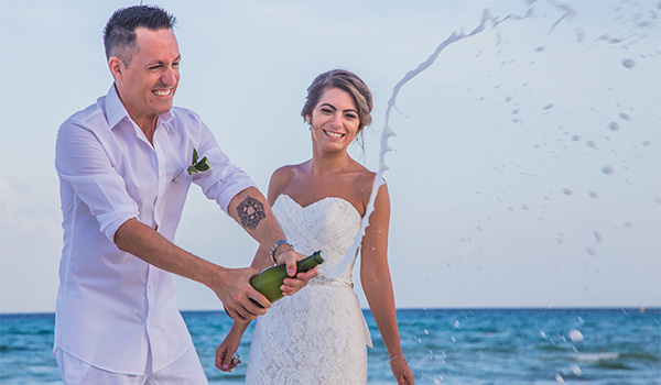 Couple popping a bottle of champagne on the beach