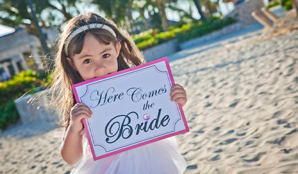 """Little girl holding up a sign that says """"Here comes the bride"""""""