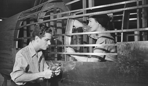 Man and woman working on an old plane
