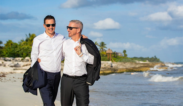 Colin and Justin walking along the beach wearing tuxedos