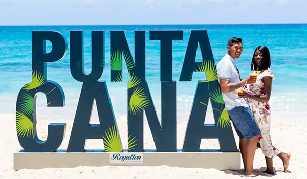Couple posing by a giant Punta Cana sign