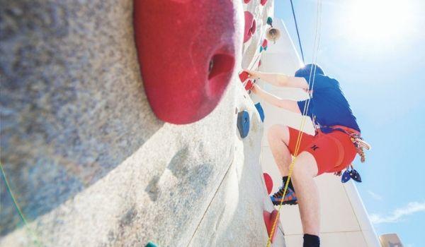Man climbing rock wall on the Marella Discovery 2 cruise ship