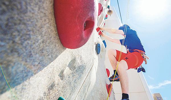 Homme grimpant un mur d'escalade sur le bateau de croisière Marella Discovery 2