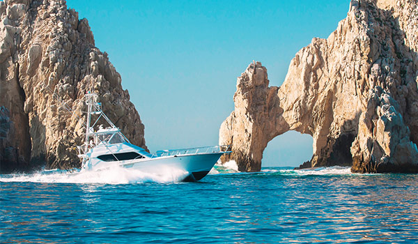 Motor boat cruising past rocky archways