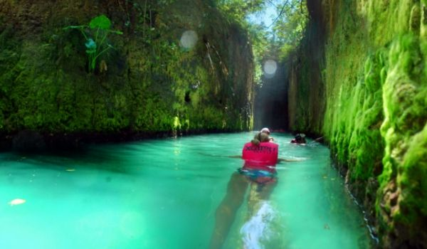Woman swimming through cenote