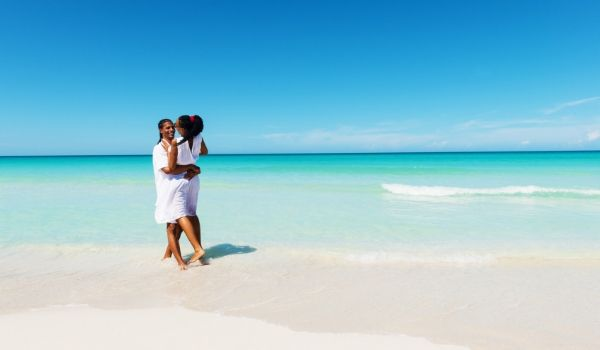 Blue skies, turquoise water, a couple on a white-sand beach