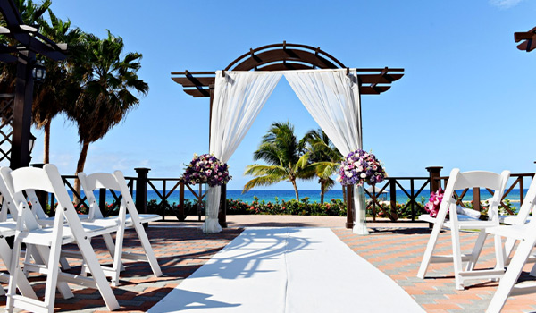 Wedding ceremony on a deck surrounded by palm trees, with the ocean in the background