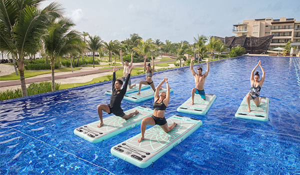 Six people doing a Royalton Fit™ class in the pool.