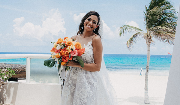 Bride posing with a tropical bouquet on the beach