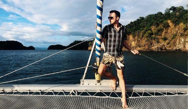Man standing on deck of a catamaran