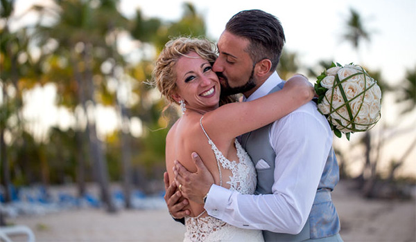 Groom kissing his bride on the cheek with the beach in the background