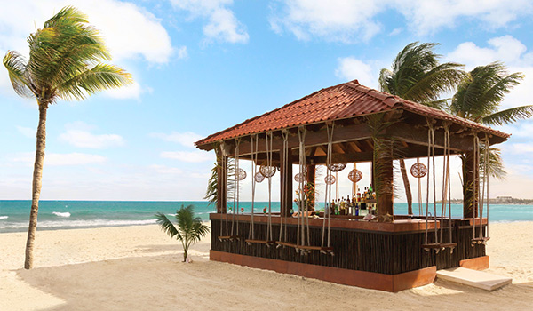 Tiny wooden bar with swing chairs located on the beach.