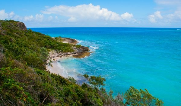 Tropical scenery in Holguin with turquoise waters. white-sand shores and lush green forests