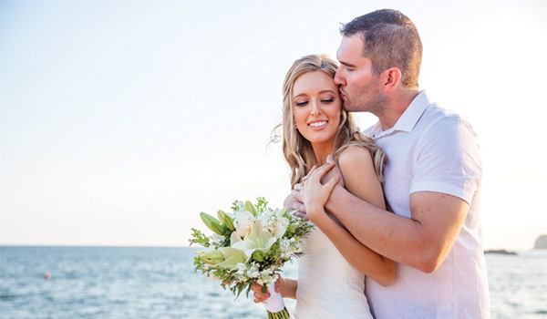 Bride and groom posing on the beach