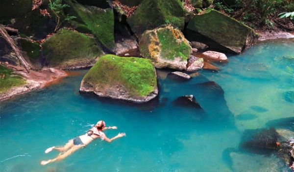 Woman swimming through crystal-clear natural pool