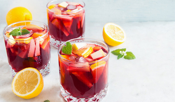Three glasses of delicious sangria topped with fruit