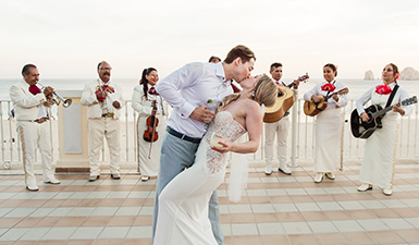 Bride and groom kissing in front of a mariachi band