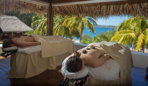 Man and woman enjoying hot stone treatment with views of the ocean