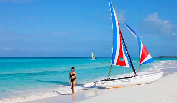Woman walking by a catamaran beached on the shore
