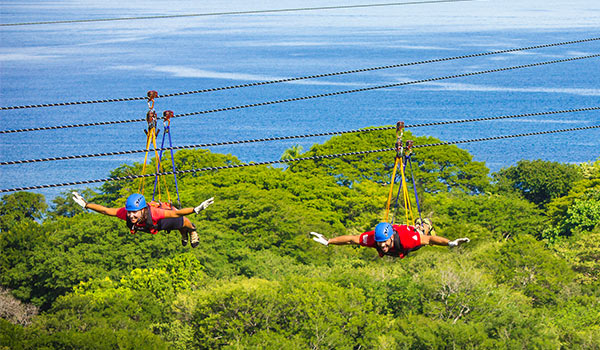 Two people ziplining above a jungle overlooking the ocean