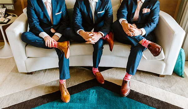 Groom and his two groomsmen getting ready for the wedding