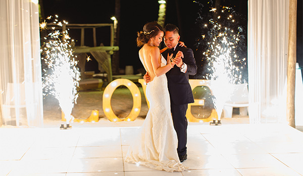 Bride and groom dancing with fireworks in the background