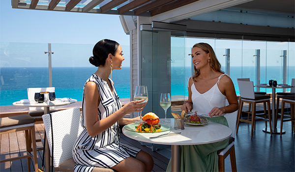 Two women enjoying lunch at a high-top table overlooking the ocean