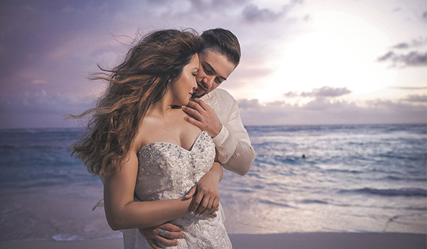 Bride and groom standing on the edge of the beach at sunset