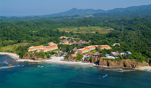Aerial view of cliffside resort with mountains in the distance