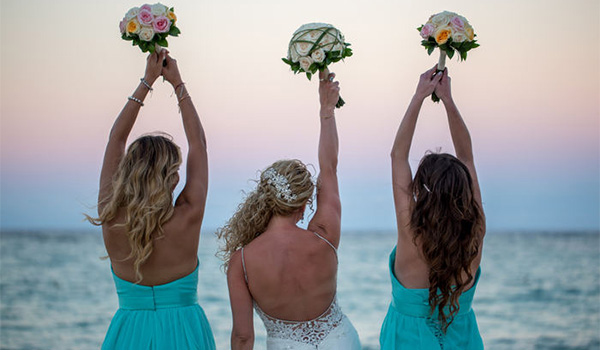 Bride and two bridesmaids holding tropical bouquets on the beach