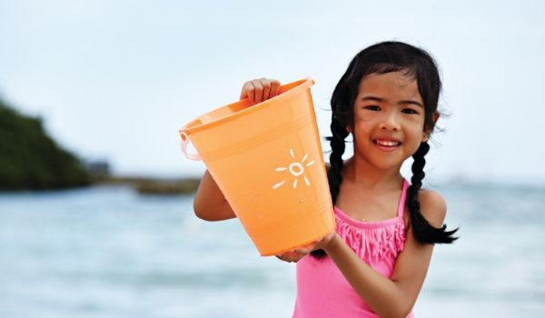 Little girl holding a bucket with a Sunwing logo on it by the ocean
