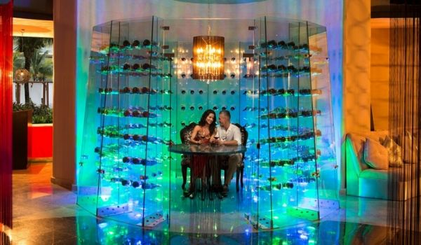 Couple dining in a lit-up romantic wine cellar